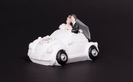 White car on a black background, just married, bride and groom