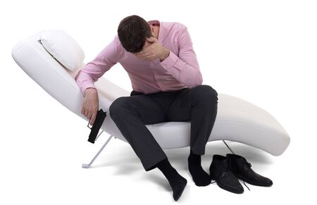Man client sitting with psychologist on the comfortable couch, handgun in had Zdjęcie Seryjne