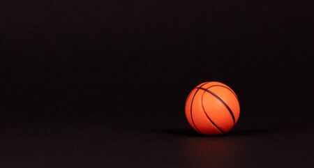 Single small rubber toy in form of basketball, isolated on black background Stock fotó