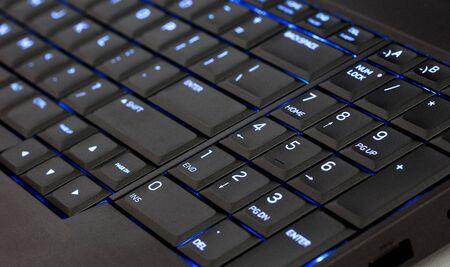 Close up led backlit computer laptop keyboard, blue Reklamní fotografie