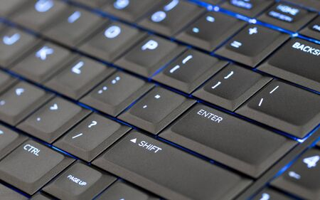 Close up led backlit computer laptop keyboard, blue