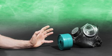 Man in room filled with smoke, trying to reach for vintage gasmask - Isolated on black - Green smoke Banco de Imagens
