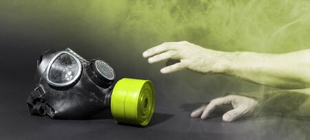 Man in room filled with smoke, trying to reach for vintage gasmask - Isolated on black - Yellow smoke 版權商用圖片 - 143947842