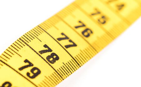 Close-up of a yellow measuring tape isolated on white - 78 - Selective focus