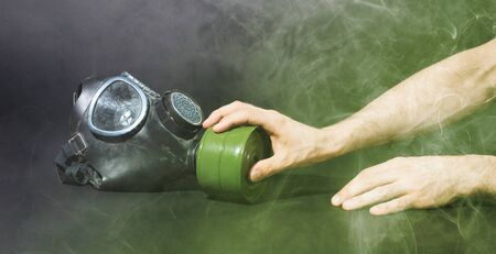 Man in room filled with smoke, trying to reach for vintage gasmask - Isolated on black - Green smoke 版權商用圖片