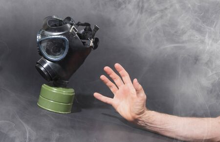 Man in room filled with smoke, trying to reach for vintage gasmask - Isolated on black - Green filter