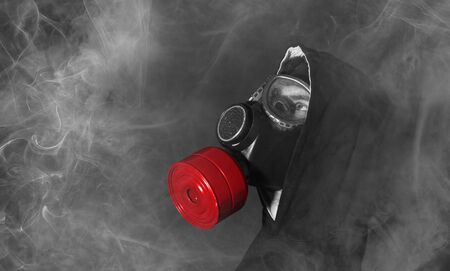 Man in a gas mask in the smoke, white smoke, red filter