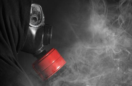Man in a gas mask in the smoke, white smoke, red filter Stock Photo