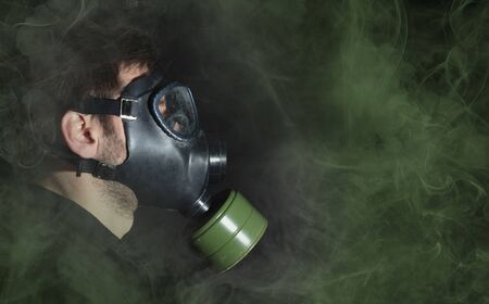 Man in a gas mask in the smoke, green smoke