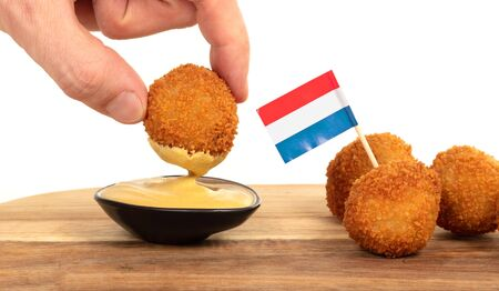 Dutch traditional snack bitterbal in a hand, isolated