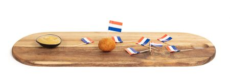 Dutch traditional snack bitterbal, just one left on a wooden serving board, isolated
