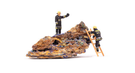 Malachite - Azurite mineral stone with a small fireman on it, isolated on white