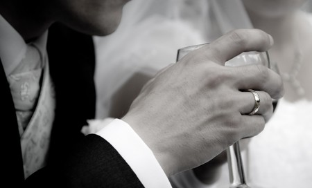 groom holding a glass of wine and going to drink photo