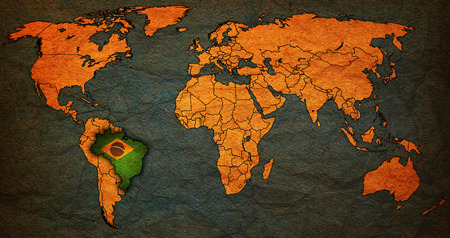 national borders: brazil flag on old vintage world map with national borders