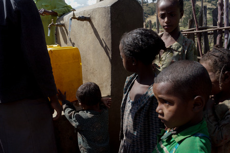 obtain: people in ethiopia near faucet with potable water