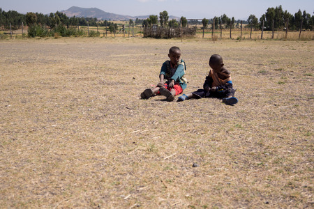 sitting on the ground: two black children sitting on a dry ground in ethiopia
