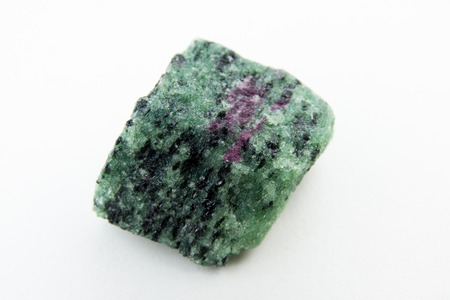 mineralogy: macro photo of ruby inside of zoisite isolated over white