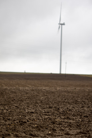 harrowing: landscape with wind turbines and plowed soil on the empty field at the end of autumn