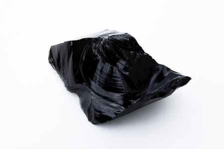 Extreme close up of Obsidian mineral isolated over white background