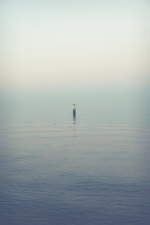 melancholic seascape single buoy on a calm sea during sunset Stok Fotoğraf