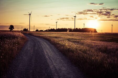landscape with dirt road through fields with wind turbine in rural area during sunset 스톡 콘텐츠