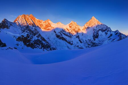 View of snow covered landscape with Dent Blanche mountains and Weisshorn mountain in Swiss Alps near Zermatt. Panorama of Weisshorn and surrounding mountains in Switzerland. Beautiful morning Imagens