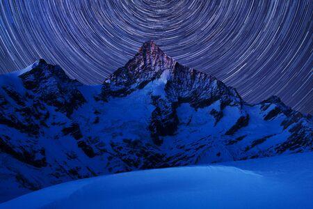 Incredible night view in Swiss Alps. Star trails moving in blue sky. Zermatt Resort location, Weisshorn, Switzerland. Landscape astrophotography background. Winter season, Christmas time