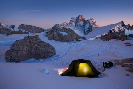 Winter camping, shining green tent on snow. Night shot, long exposure, sleeping on snow. Alps Mountains landscape panoramic view. Gorgeous winter day in Dolomites, Italy. Stock fotó