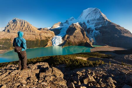 Mount Robson is the most prominent mountain bridge in the North America's Rocky Mountain range; It is also the highest point in the Canadian Rockies. Located in Mount Robson Provincial Park, British Columbia. Standing man, tourist in the landscape