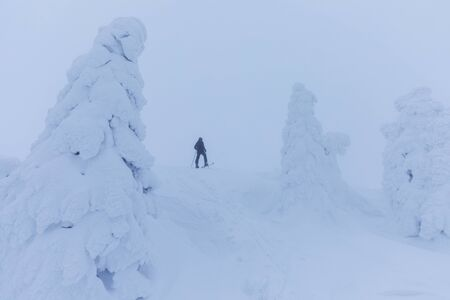 Backcountry skier pushing through fog on snowy slope. Ski touring in Harsh winter conditions. Ski Tourer Sporting in the Mountains. Winter alpine landscape