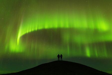Aurora Borealis and silhouette of standing lovers. Jokulsarlon, Iceland. Aurora happy man. Sky with stars and green polar lights. Night landscape with aurora and people. Concept. Nature background