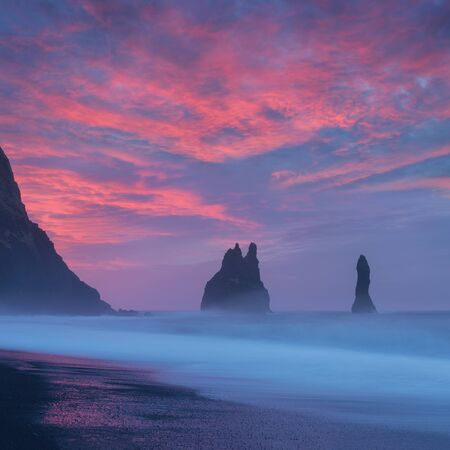 Reynisdrangar cliffs near Vik town. Dramatic landscape with Atlantic Ocean. Tourist attraction of Iceland. Rock formations on Black Beach. Reynisfjara Beach at sunrise, Halsanefhellir Sunrise