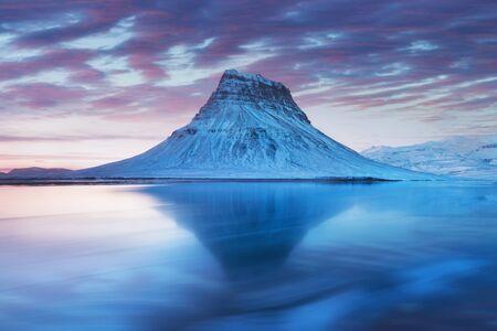 Iceland snaefellsnes peninsula and famous Kirkjufell. Kirkjufell is a beautifully shaped and symmetrical, free standing mountain in Iceland. Frozen view of Kirkjufell (church mountain). Winter scene