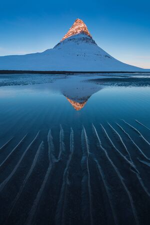 Iceland snaefellsnes peninsula and famous Kirkjufell. Kirkjufell is a beautifully shaped and symmetrical, free standing mountain in Iceland. Frozen view of Kirkjufell (church mountain). Winter season Archivio Fotografico