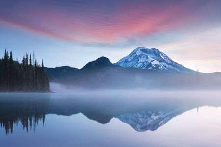 South Sister and Broken Top Reflect Over Calm Waters of Sparks Lake at Sunrise in the Cascades Range in Central Oregon, USA in an Early Morning Light. Morning mist rises from lake into trees. 스톡 콘텐츠