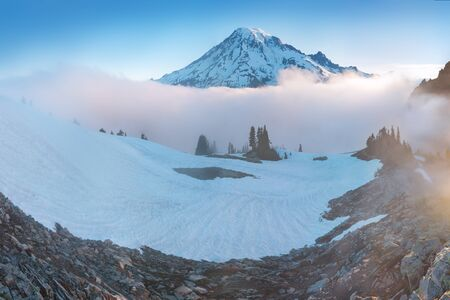 Morning light high above the cloud layer on Mount Rainier. Beautiful Paradise area, Washington state, USA in the fall with snow on Mount Rainier on a sunny day and morning with blue sky. Cascade Range 스톡 콘텐츠