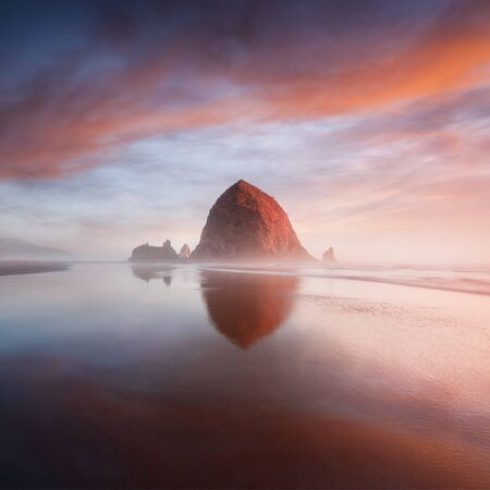 Sunset at Cannon Beach with dramatic clouds in the background and a nice reflection in the water. Dramatic coastal seascape featuring scenic rock formations in Haystack Rock Oregon, USA Summer season