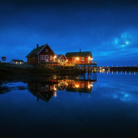 Fishing town Reine reflecting at night on Lofoten islands in Norway, above the Arctic Circle Winter landscape with buildings, blue cloudy sky reflected in water at dusk. Norwegian rorbuer Summer sea