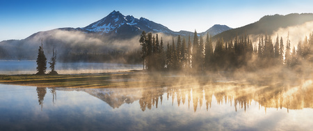 South Sister and Broken Top Reflect on the Spm Lake at Sunrise in Cascades Range in Central Oregon, USA Morning mist rises from lake to trees