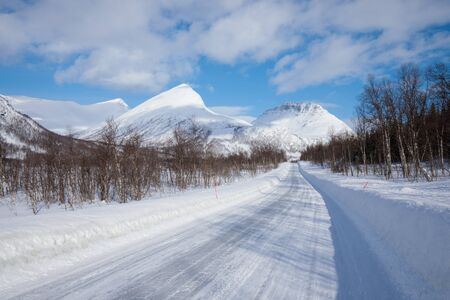 Fresh snow on the Troms county after a short winter in May. Beautiful frosty landscape in winter Winter landscape in norway or sweden during sunny day road and scenic landscape in Alps mountains