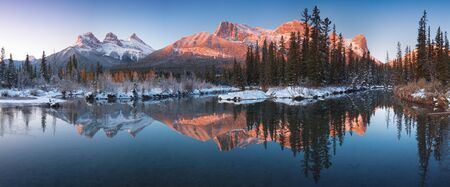 The first snow Almost the perfect reflection of the Three Sisters Peaks in the Bow River. Canff in Banff National Park Alberta Canada Snow covered winter mountain in a winter atmosphere. Beautiful day