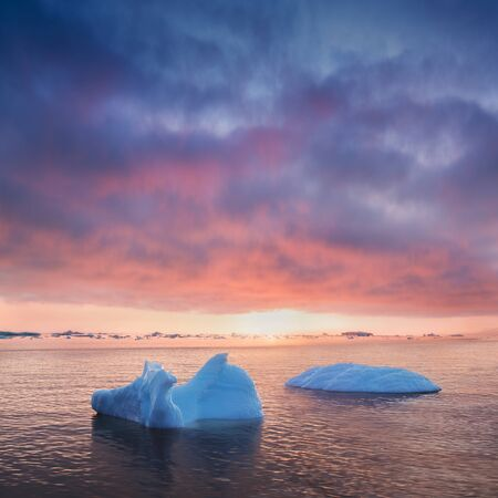 Stranded icebergs in the fog at the Icefjord near Ilulissat. Nature and landscapes of Greenland. Travel on the vessel among ices. Phenomenon of global warming. Coast in the sunset. Banque d'images