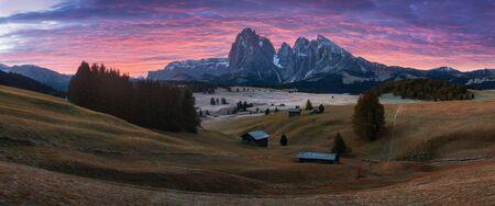 Scenario aereo di alba autunnale con larici gialli e piccolo edificio alpino e Odle - gruppo montuoso delle Odle sullo sfondo. Alpe di Siusi (Alpi Dolomitiche, Italia). montagne dolomitiche