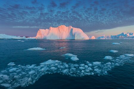 Photogenic and intricate iceberg under an interesting and blue sky during sunset. Effect of global warming in nature. Conceptual image of melting glacier in deep blue water in Antarctica or Greenland