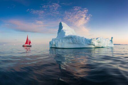 Un petit bateau parmi les icebergs. Croisière en voilier parmi les icebergs flottants dans le glacier de la baie de Disko pendant le soleil de minuit Ilulissat, Groenland. Etude du phénomène de réchauffement climatique Glaces et icebergs Banque d'images