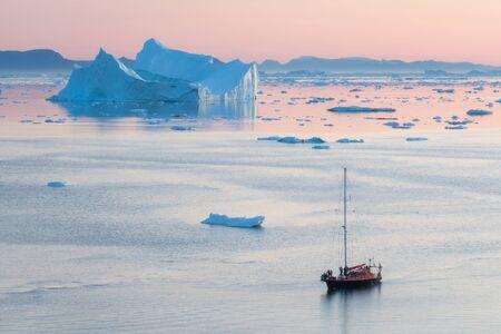 Little Red Sailboat Cruising Among Floating Icebergs In Disko Bay Glacier During Midnight Sun Season Of Polar Summer. Ilulissat, Greenland. UNESCO world heritage