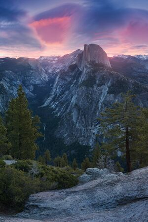 Half Dome and Yosemite Valley in Yosemite National Park during a colorful sunrise with trees and rocks. California, USA Sunny day in the most popular viewpoint in Yosemite Beautiful landscape background Stock Photo
