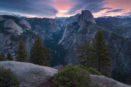 Half Dome and Yosemite Valley in Yosemite National Park during colorful sunset with trees and rocks. California, USA Sunny day at the most popular viewpoint in Yosemite. Beautiful landscape background