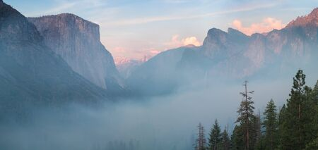 Classic Tunnel View of scenic Yosemite Valley with famous El Capitan and Half Dome rock climbing summits in beautiful misty atmosphere at summer, Yosemite National Park, California, USA