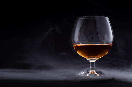 Photo of cognac glass in a smoke against black background 免版税图像